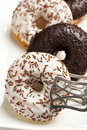Chocolate sprinkle donuts black and white with pastry tong closeup Royalty Free Stock Photography