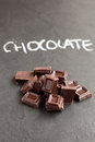 Chocolate squares closeup of pile of with word written in chalk on dark background Royalty Free Stock Images