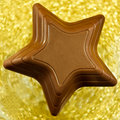 Chocolate star macro view of on blurred golden background Stock Images