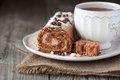 Chocolate swiss roll cake with coffee cream and a cup of tea on a wooden background selective focus Stock Image