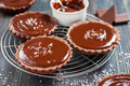 Chocolate tarts with salted caramel on a dark wooden background in rustic style Stock Photos