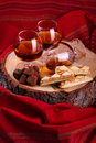 Chocolate truffle and cognac with brandy balloon pastries puff pastry on pine stump with red cloth background Stock Photo