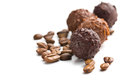 Chocolate truffles with cocoa beans on white background Stock Photos