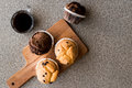 Chocolate and Vanilla Muffins with coffee on wooden surface.