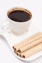 Chocolate wafer cream rolls and white cup of black coffee Royalty Free Stock Photo