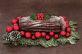 Chocolate yule log with red bauble decorations holly snow covered fir and pine cones over brown handmade lokta paper background Royalty Free Stock Photo