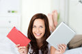 Choice of a book or e book smiling happy young woman holds up and tablet pc with an as she tries to decide which is the best Stock Image