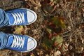 Choose the best A conceptual picture illustrating the teenager`s problem in the life choices. Legs in blue sneakers and blue jean Royalty Free Stock Photo