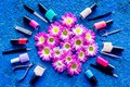 Choose nail polish for manicure. Bottles of colored polish on blue background top view