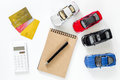 Choosing car concept. Toy cars and bank card on white background top view