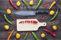 stock image of  Chopped cayenne chilli pepper on cutting board with knife and other peppers all aaround