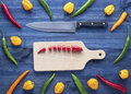 Chopped chilli peppers on blue wooden table. Royalty Free Stock Photo