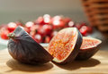Chopped Fig fruits on the cutting board with briar (dog rose) on Royalty Free Stock Photo