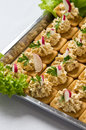 Chopped fish salad on crackers and cracker appetizers topped with and sliced radishes Stock Photos