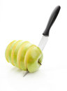Chopped green apple sharp knife cut into pieces of on a white background Stock Images