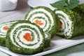 Chopped green spinach roll filled and cream cheese on a white plate close up horizontal Royalty Free Stock Photo