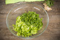 Chopped lettuce in a glass bowl on the old wooden table Royalty Free Stock Images