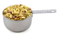 Chopped pistachio nuts in a metal cup measure Royalty Free Stock Photo