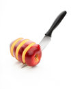 Chopped red apple sharp knife cut into pieces of on a white background Royalty Free Stock Image