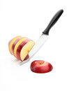 Chopped red apple sharp knife cut into pieces of on a white background Royalty Free Stock Photography