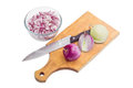 Chopped red onion, bulb onions and knife on cutting board Royalty Free Stock Photo