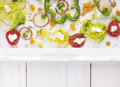 Chopped summer vegetables in tray with patterned border on white wooden table top view Royalty Free Stock Photos