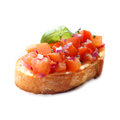 Chopped tomato and onion bruschetta an italian antipasta served on grilled or toasted crispy crusty sliced baguette on a white Stock Photos