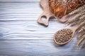 Chopping board wheat rye ears bread stick wooden spoon corn Royalty Free Stock Photo