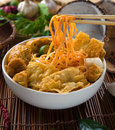 Chopstick and curry noodles laksa with plenty of raw ingredients as background Stock Image