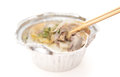 Chopsticks catching a piece of chicken with a fast food bowl Royalty Free Stock Photo