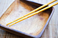 Chopsticks and empty wooden dish Royalty Free Stock Photo