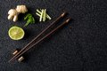 Chopsticks and food ingredients on black stone table top view Royalty Free Stock Photo