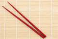Chopsticks red over bamboo mat background Royalty Free Stock Photography