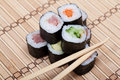 Chopsticks and sushi on bamboo mat Stock Photos