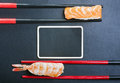 Chopsticks and two sushi with salmon and shrimp on a black backg Royalty Free Stock Photos