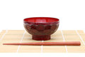 Chopsticks with wooden bowl on bamboo mat background Royalty Free Stock Images