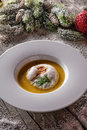 Chrismas fish soup in white plate with christmas decorations, modern gastronomy Royalty Free Stock Photo
