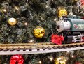 Christams train before christmas tree with balls Royalty Free Stock Photo