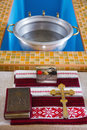 Christening ceremony in russian church holy bible orthodox cross and bowl prepared for Royalty Free Stock Images