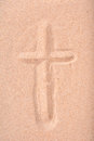 Christian cross drawn in dry sand a jesus with finger into Stock Photography