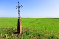 Christian cross in a field green grassy under the blue sky Stock Image