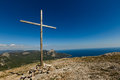Christian wooden cross on mountain top, rocky summit, beautiful inspirational landscape with ocean, clouds and blue sky Royalty Free Stock Photo