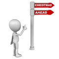 Christmas ahead words on a road sign little d man pointing towards it against white background Royalty Free Stock Photo