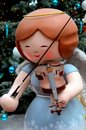 Christmas angel statue with wings in blue dress plays violin with bow Royalty Free Stock Photo