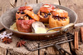 Christmas apples baked stuffed with raisin and nuts for with vanilla sauce on a old rustic pan on wooden table Stock Image