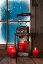 Christmas atmosphere four red burning candles in the window with a old tin lantern decorated on a wooden sill Stock Photo