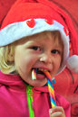 Christmas baby with candy on the red background Royalty Free Stock Images