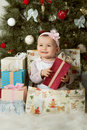 Christmas and baby girl one year old little solemnize sit under tree with gift vertical photo Royalty Free Stock Image