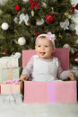 Christmas and baby girl one year old little solemnize sit under tree with gift vertical photo Royalty Free Stock Photo
