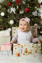 Christmas and baby girl one year old little solemnize sit under tree with gift vertical photo Stock Photo